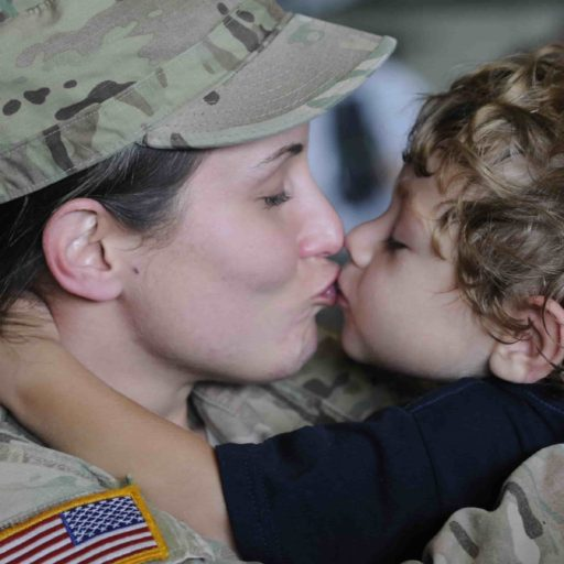 Service member kissing their child