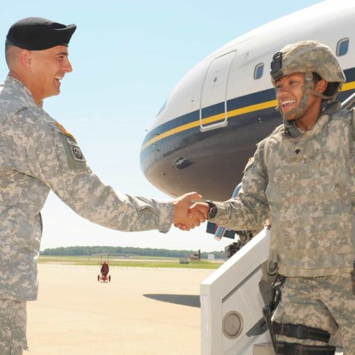Service Members shaking hands outside of a plane