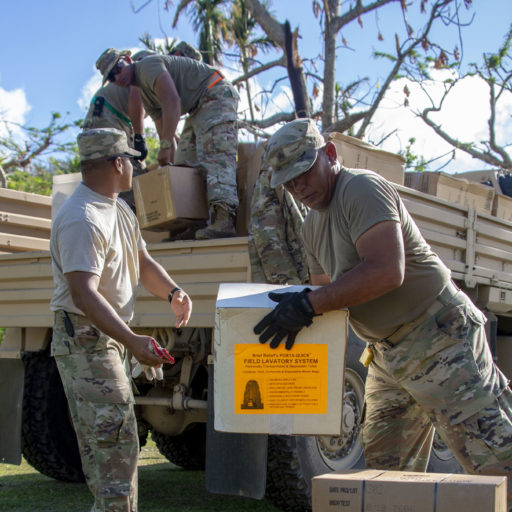 Service members working together to remove equipment from truck