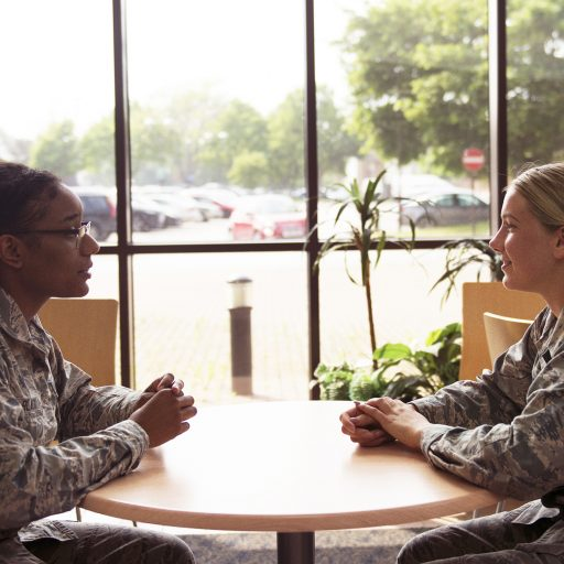 Two female soldiers talking at café